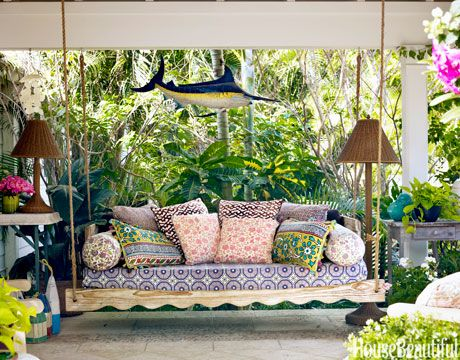 Back Porch:Contractor Tim Givens built the swinging daybed on the back porch of Liza Pulitzer Calhoun's Palm Beach house, and she simply covered its seat with a favorite tablecloth. The pillows are from Anthropologie and Roberta Roller Rabbit. The swordfish was found in an antiques shop.