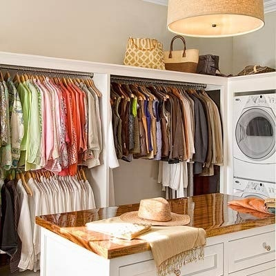 Laundry room with hanging space and table for folding clothes.