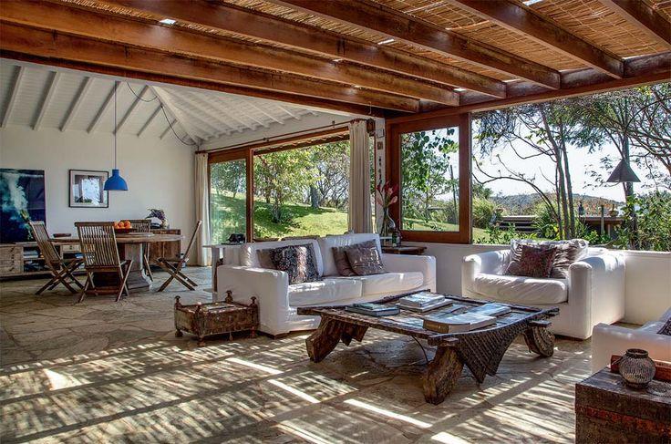 """No inverno, o morador retira o forro de palhinha do pergolado. """"A casa precisa desse sol gostoso"""", fala. Ao fundo, é possível vislumbrar o telhado inclinado da entrada, que deixa à vista o madeiramento da estrutura e foi forrado com lambri branco."""