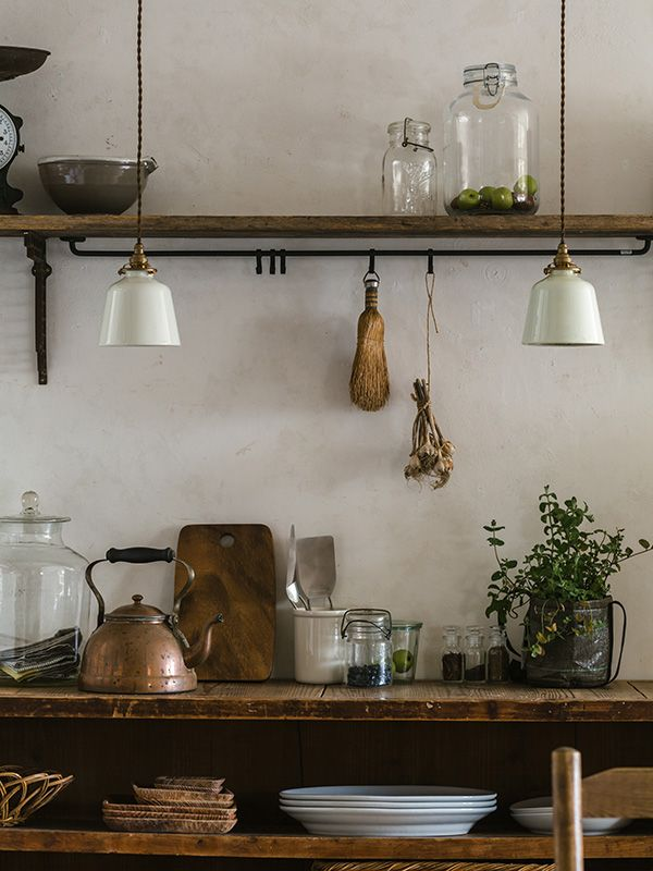 White pendant light fixtures, wood shelves and cabinets, architectural salvage, plaster walls