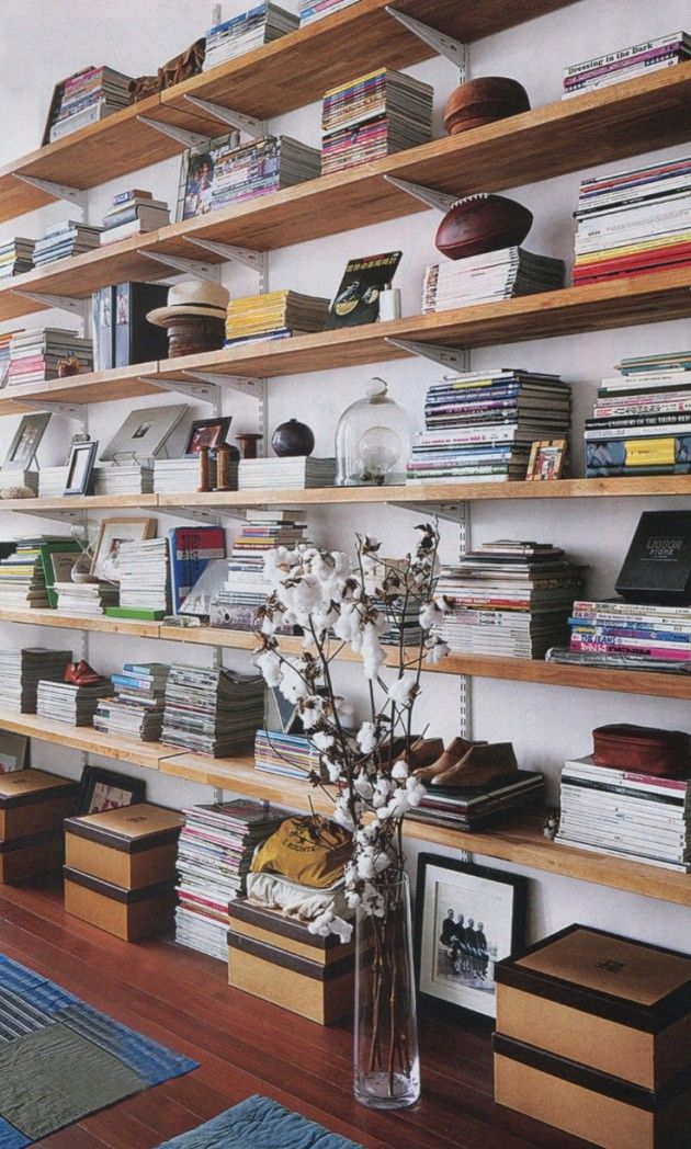 A marvelous bookshelf wall made simply of wood slabs hung with metal brackets and filled with books and other favorite things. An example of how you can make your own more beautiful without spending a fortune......V