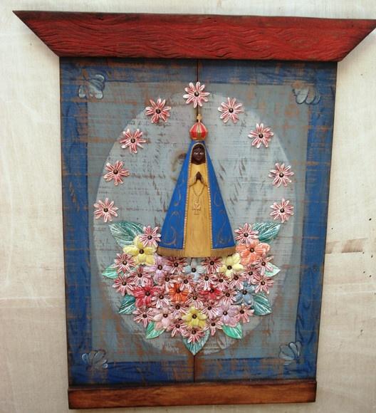 Painel Nossa Senhora Aparecida em madeira de demolição; Aparecida entalhada na madeira; decorado com flores de lata em pátina colorida. R$420,00