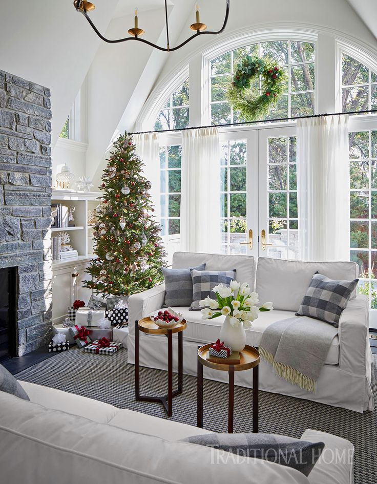 The sunroom is the perfect spot for a touch of holiday cheer, including a tree on one side of the gray stone fireplace. - Photo: Werner Straube / Design: Soledad Zitzewitz