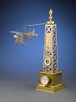 """Incredibly rare French automaton timepiece pays homage to the first flying machines   Features an airplane that flies with a revolving propeller, around the gantry   The rare gantry houses a clock, thermometer and barometer   An almost identical clock was housed at the Time Museum, Rockford, Illinois   Circa 1910   19"""" high"""