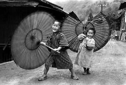 Kids fooling around with traditional umbrellas, one broken. Japan. Ken Domon