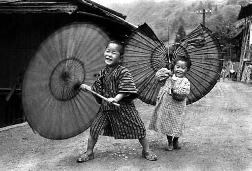 Kids fooling around with traditional umbrellas, one broken. Japan. Ken Domon