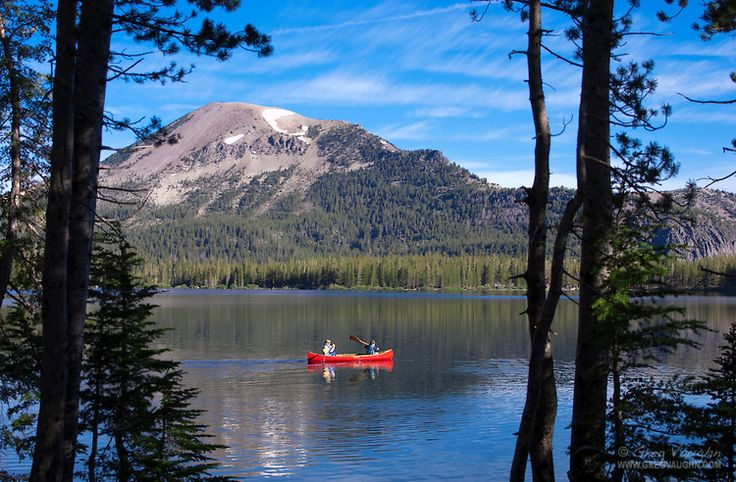 Boy and girl paddling red canoe on Lake Mary; Mammoth Lakes, Eastern Sierra Nevada Mountain, California.