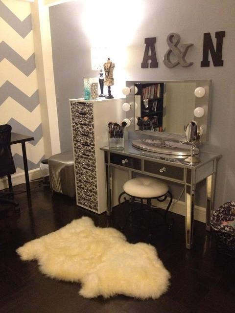 A mirrored vanity, classic Hollywood vanity lights, white fur, chevron wall, initials.