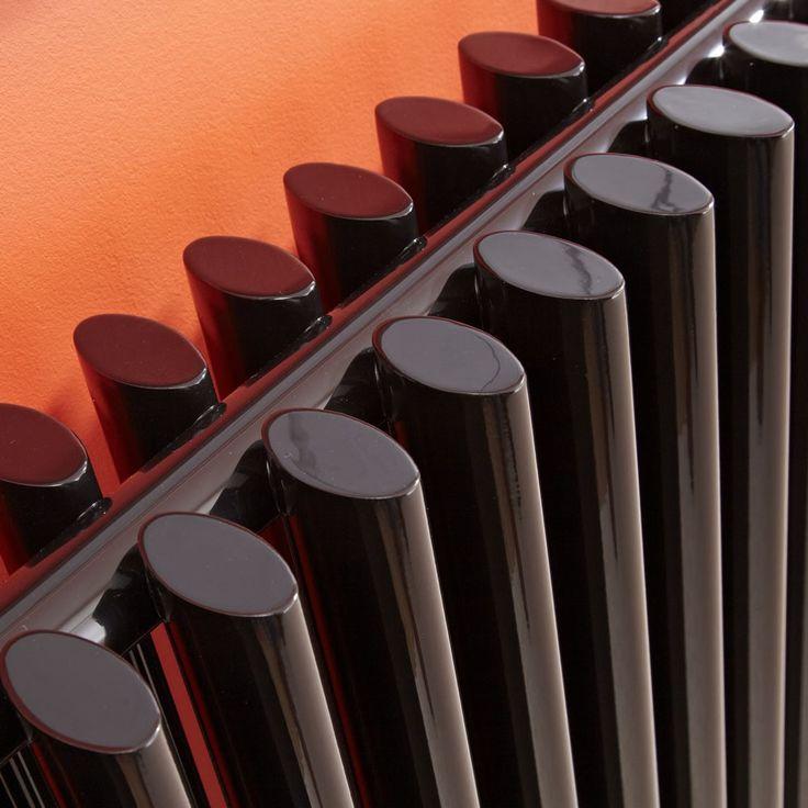 A close up of a gorgeous, high-gloss black designer column radiator.