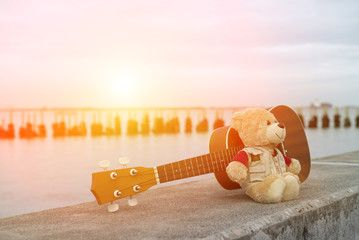 Ukulele and teddy bears on a seaside evening.
