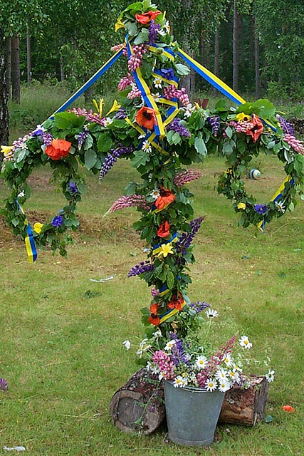 Midsummer - Midsummer  / AND May Day (May 1st)  the ribbons represent the flag -- this one is Swedish -- the 2 wreaths hang on the T shape pole -- w/vines  flowers wrapped around it all -- There's a ribbon winding around to music with Folk in National Costumes from their regions.