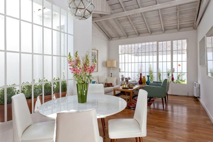 Una casa fresca y llena de gracia  En pos de aumentar la luz natural, se reemplazaron las antiguas ventanas, pequeñas, por grandes aberturas de carpintería de hierro y vidrio repartido que, también, hacen las veces de rejas