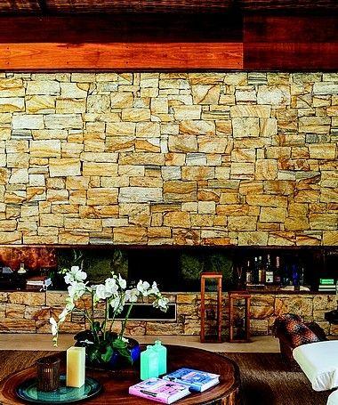 Sala de estar: a parede de pedra madeira abriga, no nicho horizontal, a lareira elétrica, indispensável no inverno. Embutido na viga de madeira, o telão desce ali para as sessões de filmes. arquiteto Thiago Bernardes