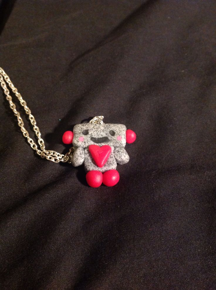Polymer clay robot. Made with granite clay and rose quartz.