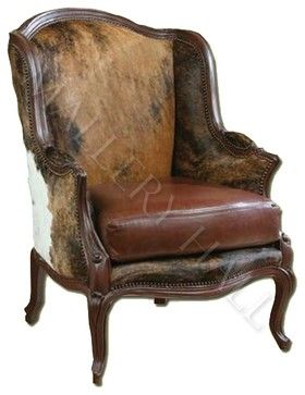 "Custom-made straight-back club chair covered in light browns cowhide, trimmed in carved wood. Specifications: Width: 29"", Depth: 36"", Ht: 41"""
