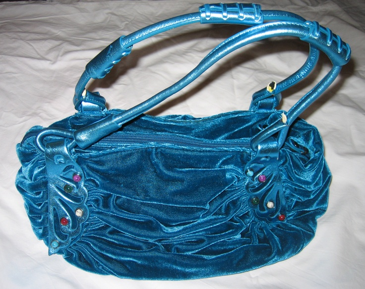 Opvallende blauwe handtas van velours en leer, afgezet met kralen.