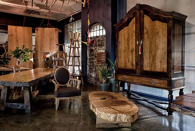 The Pierre Cronje showroom in Wynberg, Cape Town - 1½ Wolfe st, Chelsea Village. (A Gable top Cape Armoire stands over a coffee table made from a large Yellowwood trunk, an Ovalback armchair, and a Hampton dining table)