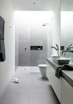 grey floors/ shower. White walls. Grey bench top