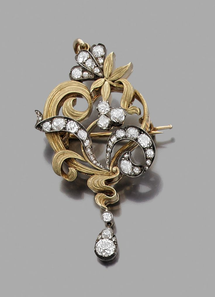 Fabergé 14K gold and silver pendant / brooch decorated with foliage and scrolls, set with old cut diamonds. Circa 1900.