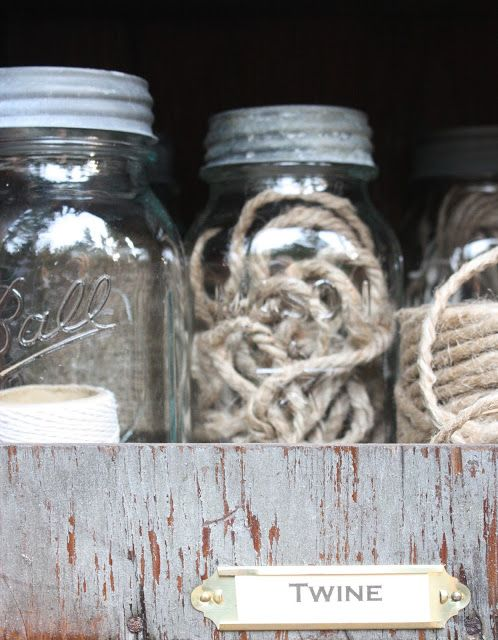 Labeled cubbies on top of potting bench.  Supplies are stored in jars for dry-keeping.