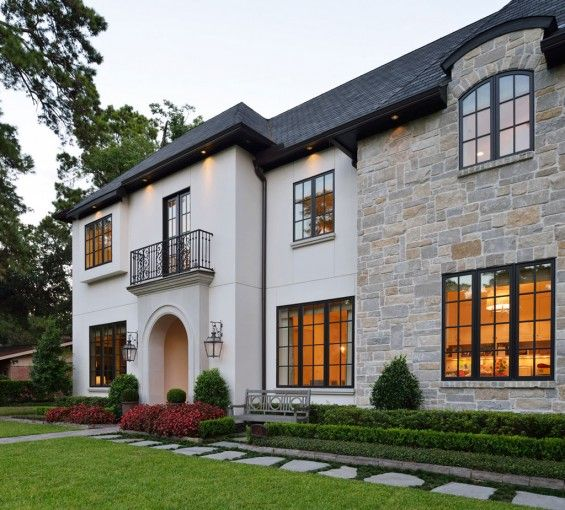 The French country transitional style architecture of this home is accentuated by Chateau Domingue lanterns and iron doors by Durango Door.