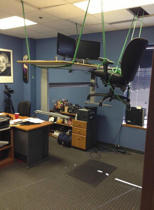 40 Hilarious Office Pranks At Places Where You Don't Want to Work,  raise desk and chair with ropes to ceiling of office,