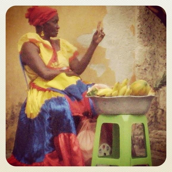 Esta mujer estuvo vendiendo frutas tropicales en Cartagena - Una ciudad por la costa Colombiana! El vestido es de los colores de la bandera Colombiana!