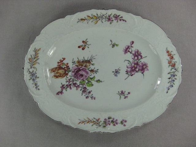 A finely decorated  Chelsea  moulded edge oval shaped  dish  painted with a rose and a tulip and with other garden flowers. Brown line to rim. Red Anchor mark   Circa  1760 Width  9 3/4""