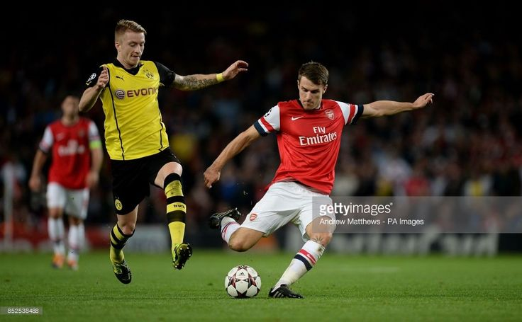 Arsenal's Aaron Ramsey (right) gets a shot on goal past Borussia Dortmund's Marco Reus (left) during the UEFA Champions League, Group F match at the Emirates Stadium, London.