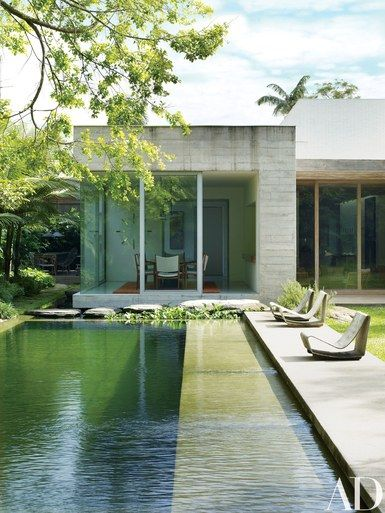 The swimming pool features a chemical-free filtration system, utilizing a separate regeneration area filled with aquatic plants and fish for water purification; the poolside lounges are Willy Guhl cement Loop chairs | archdigest.com