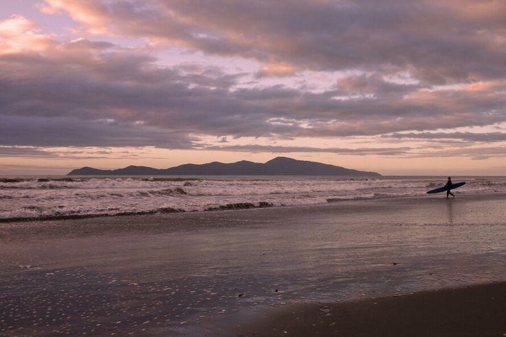 Kapiti Island and surfer Paekakariki beach NZ.