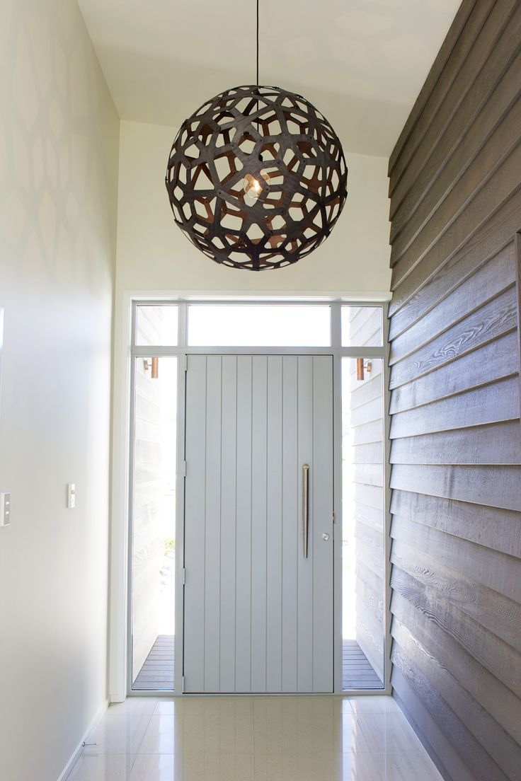 Interior weatherboard brings the outside in through this entry. Paired with a striking light fixture - G.J. Showhome