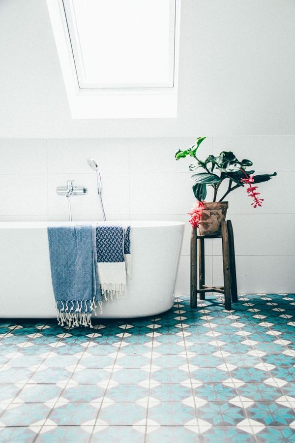 White bathroom with teal patterned floor freestanding