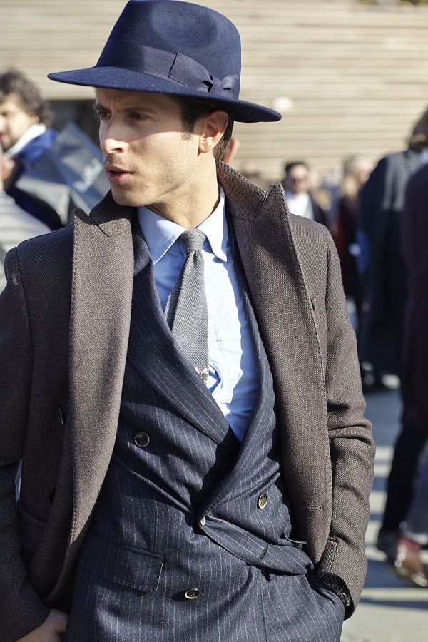 Shop this look on Lookastic:  http://lookastic.com/men/looks/hat-dress-shirt-tie-double-breasted-blazer-overcoat/7782  — Navy Wool Hat  — White Dress Shirt  — Grey Knit Tie  — Navy Vertical Striped Double Breasted Blazer  — Dark Brown Overcoat