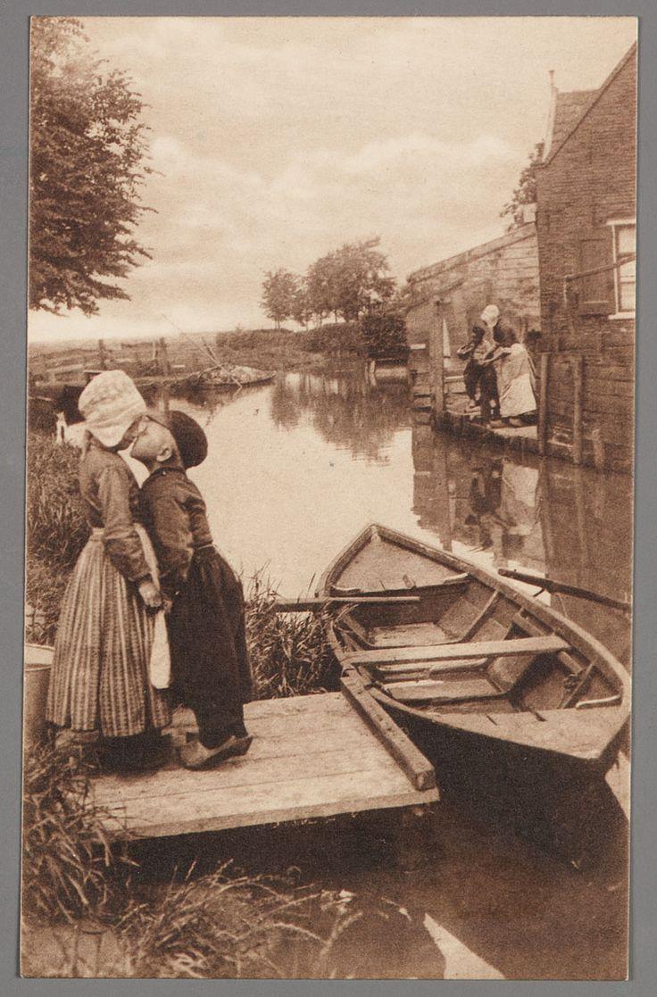 Meisje en jongen in dracht (Grietje en Jan) geven elkaar een kus. Bij de steiger het boerenroeibootje. Aan de overzijde twee mensen in dracht op het erf. 1905-1920 #NoordHolland #Volendam
