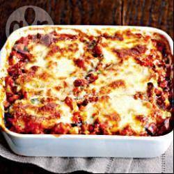 Foto recept: Italiaanse aubergine/mozarellaovenschotel Nodig: 2 aubergines in de lengte snijden en in gedeelten bakken in olie,2 min per kant,700 gr tomatensaus ,schenk een laag in een ovenvaste schaal,leg er 2 -3 plakken aubergines op,herhaal dit en eindig met tomatensaus.Leg hierop plakken mozzarella en bestrooi met 50 gr parmezaanse kaas. Bak de schotel in een oven van 200 gr gedurende 20 min. Bestrooi met basilicum,lekker met ciabatta en een groene salade.