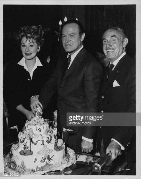 """Lucy, Bob Hope, & Jack Warner cut the cake on the set of """"Critic's Choice"""""""
