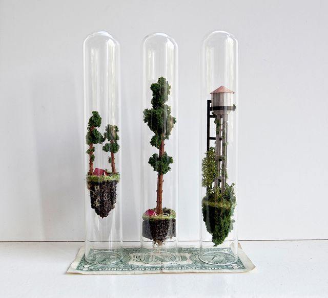 Artist Rosa de Jong continues to explore the spacious confines of glass test tubes by erecting impossibly small buildings, trees, and other inhabitable structures inside of them. For her series titled