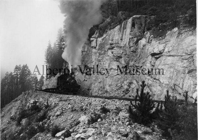 Log train returning to the woods with empty cars, c.1941.  Photographer: Leonard Frank.  [Alberni Valley Museum Historic Photo Collection PN20111]