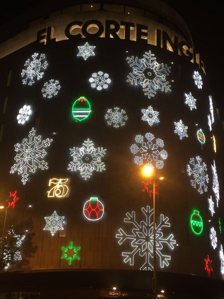 This is the El Corte Ingles building in Placa Catalunya. The snowflake decorations as well as the ornaments have popping colors with white, green, and red as well. It also is sparkling around the vicinity of the snowflakes as well.