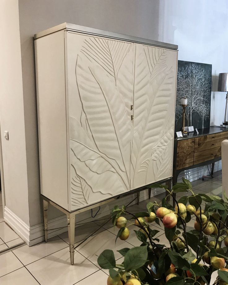 """Барный шкаф """"Palms Up!"""" сочетает в себе артистизм и естественность. Светлые дверные панели украшены резным рельефом ручной работы в виде пальмовых веток, которые будут создавать потрясающий визуальный фокус в вашей столовой. Внутри шкафа находится бар с подсветкой. #caracole #dom_mebeli_kiev"""