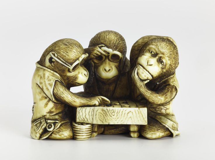 Netsuke of carved ivory, three monkeys seated round a go board with two wearing spectacles: Japan, by Tamatoshi.