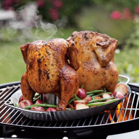 Vertical chicken roaster holds two birds and has a pan for vegetables.