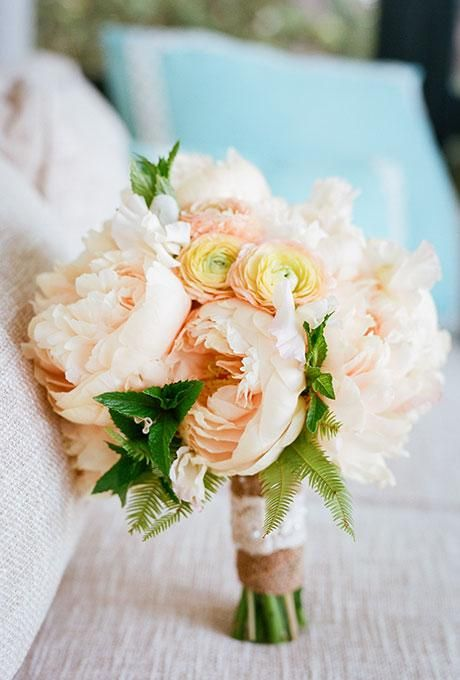 Pops of greenery punch up this wedding bouquet with peach peonies and ranunculuses   @oohevent   Brides.com