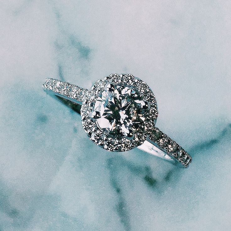 This amazing halo diamond engagement ring features small round brilliants that encircle the centre diamond and decorate the band to create maximum impact and sparkle.