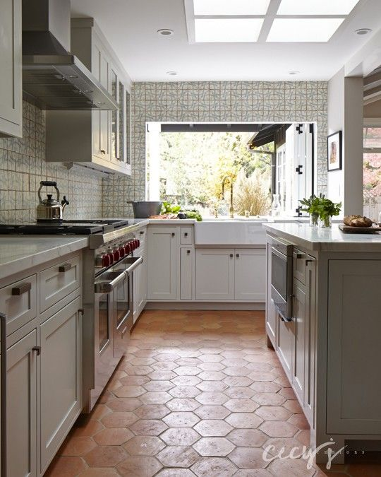 rustic cottage kitchen features four skylights situated over an island topped with white marble lined atop tile floor - Kitchen Floor Tile Design Ideas