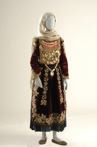 Women in Salamina wore their bridal costume to all festivals for one year following their wedding until the birth of their first child. It resembles the Megara costume and those of other regions featuring the Renaissance-style gown. The white cotton chemise has lace decoration at the neckline, cuffs and hem. On top of this is worn a velvet zipouni (short jacket) embroidered with fine gold cord and a sleeveless dress with a bodice of crimson velvet and full, gathered skirt of hases…