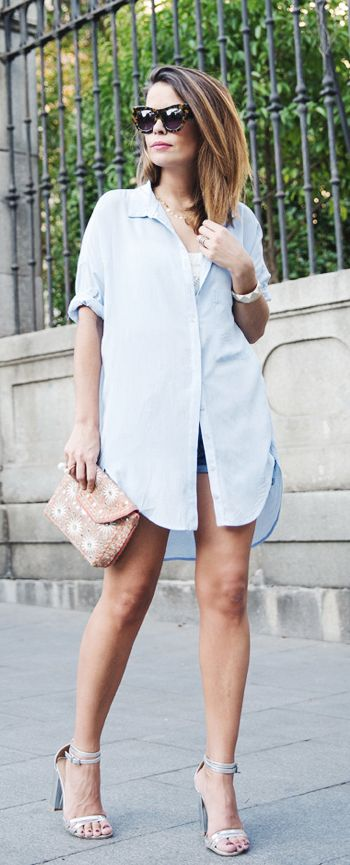 Sara Escudero is wearing an oversized pale blue boyfriend shirt from Bershka, short from Levi's, shoes from ASOS and the purse is from Antik Batik