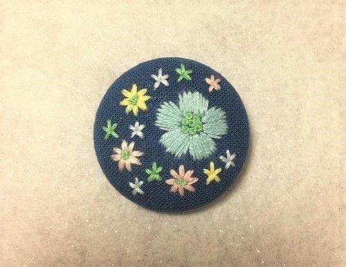 手刺繍をほどこしたブローチです。くるみボタンの金具で制作しているので、軽くてニットやショールにつけても下がりにくいのが特徴です。■大きさ 直径約38ミリ■生地の色 ダークブルー