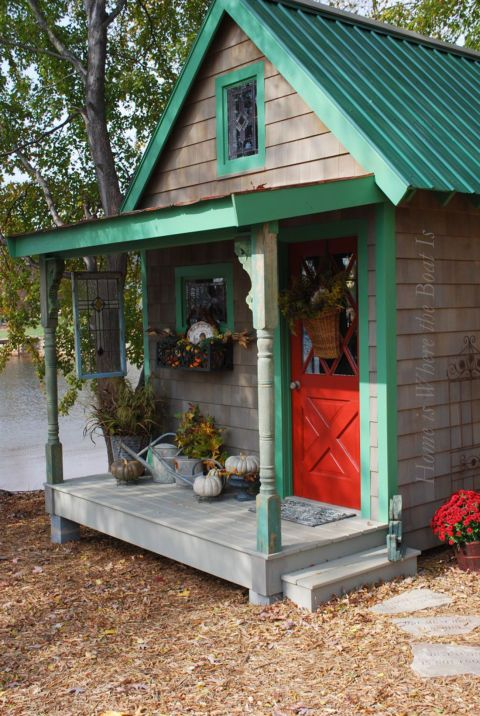 Blogger Mary combines old and new on the front porch of her garden shed by pairing a bright red door with baskets of seasonal blooms.  See more of this shed at Home is Where the Boat Is.